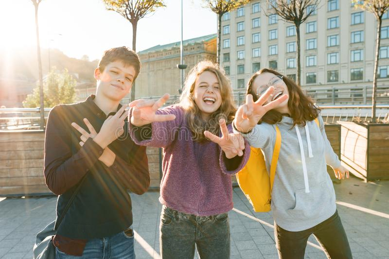 Portrait of friends teen boy and two girls smiling, making funny faces, showing victory sign in the street. City background, stock images