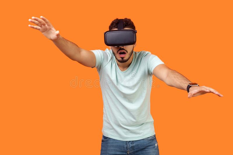 Portrait of frightened gamer, brunette man stretching hands forward, trying to grab something while playing virtual reality game royalty free stock photography