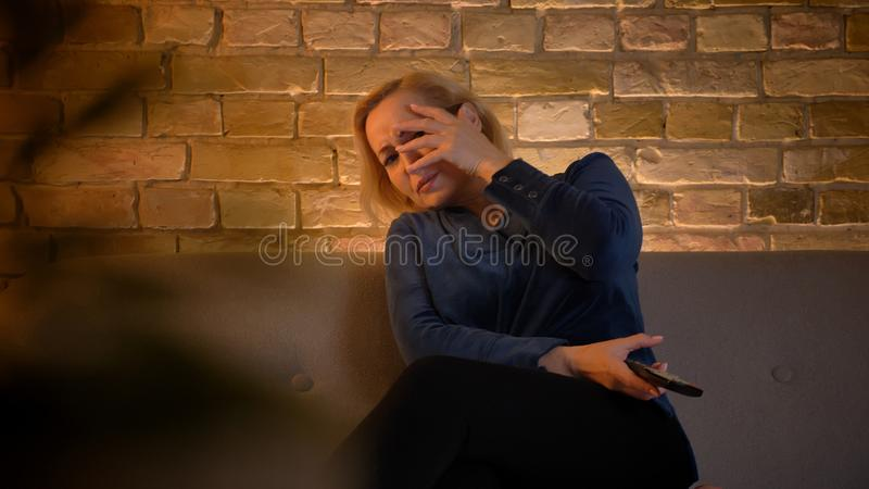 Portrait of frightened senior caucasian lady watching horror movie and hiding by her hand in cozy home atmosphere. Portrait of frightened senior caucasian lady royalty free stock photos