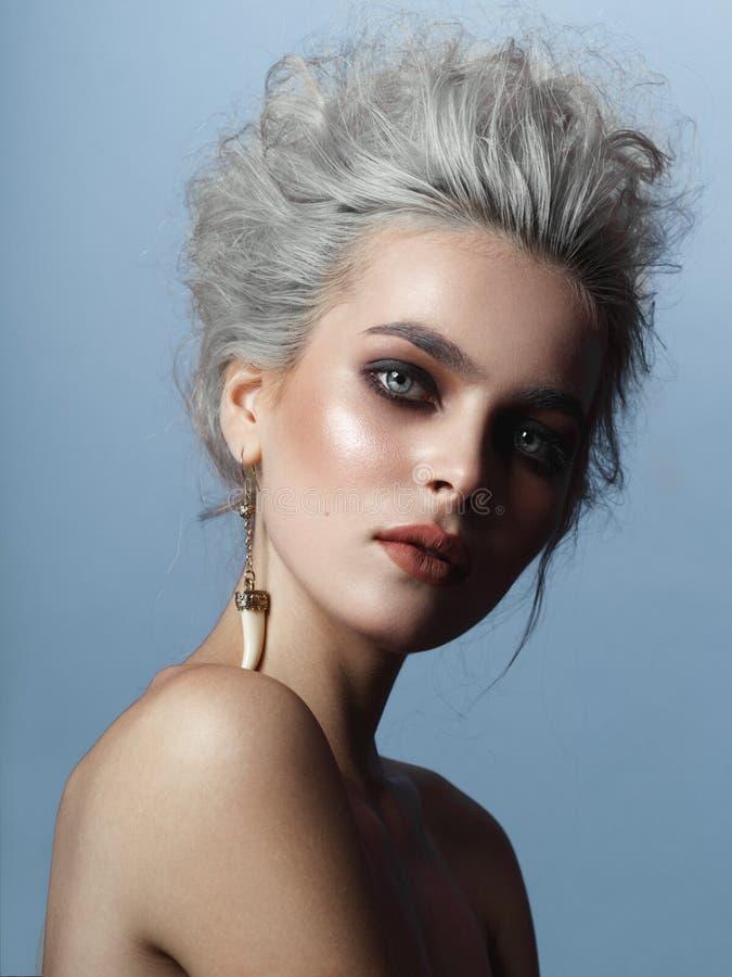 Portrait frontal de jeune femme élégante, de maquillage parfait et de coiffure blonde grise, sur un fond bleu photographie stock
