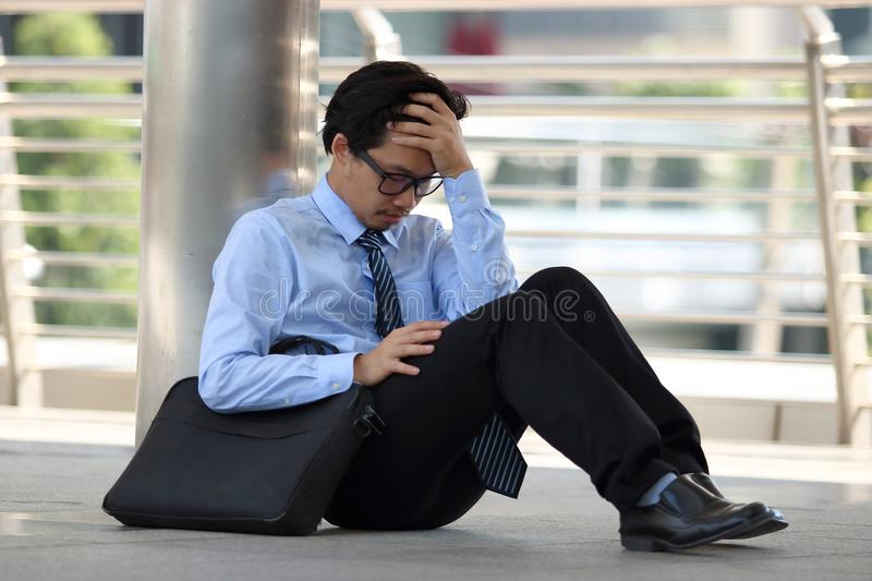 Portrait of frustrated stressed young Asian man sitting on the floor of sidewalk office and feeling tired with job royalty free stock image
