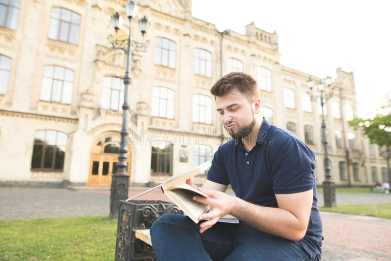 Portrait of a frustrated student sitting on a bench at a university campus with books and studying royalty free stock photos