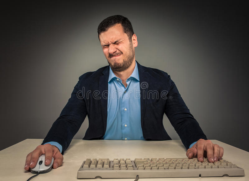 Portrait frustrated young man, with closed eyes and pursed lips. Sitting at a desk near a computer, isolated on gray background. Feeling sick and tired - Human stock images