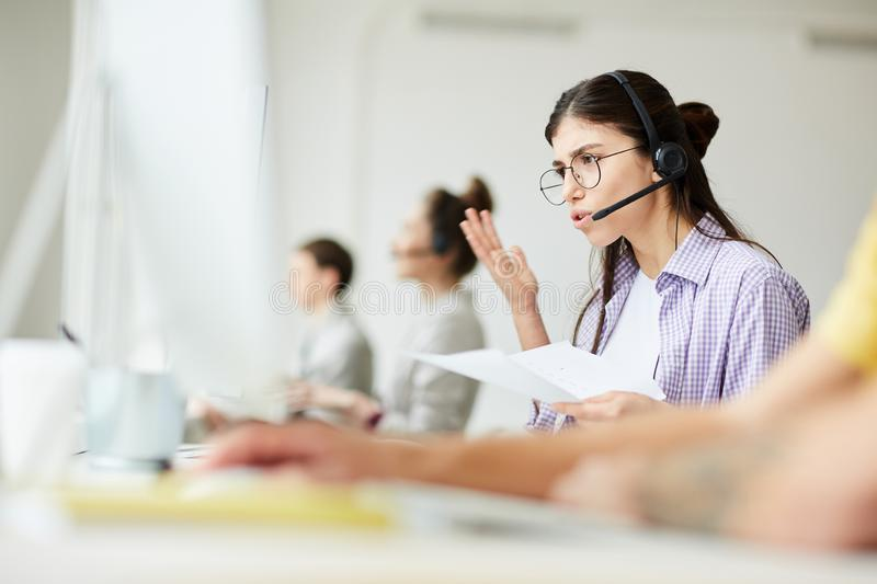 Frustrated Hotline Operator. Portrait of frustrated young women answering client calls while working at support line, copy space stock photography