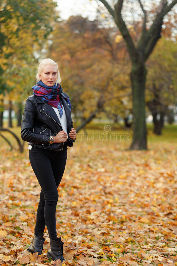 Portrait in full growth of young blonde woman walking outdoors stock photography