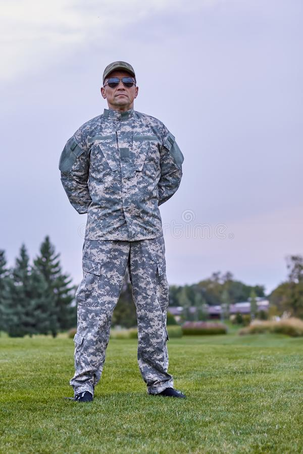 Portrait of full-length army officer in the park. Severe serious commander in camouflage stock image
