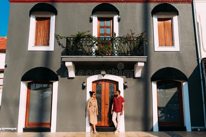 Portrait of a full length stylish bearded man and his wife standing near the building stock photography