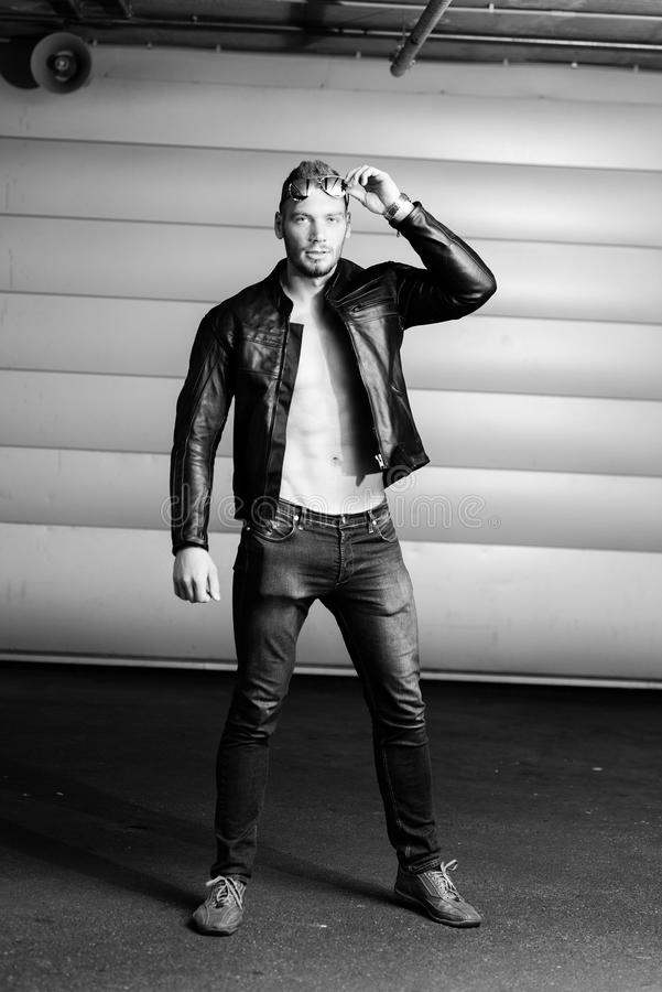 Portrait in full-length white athletic men in a black leather jacket and dark glasses. royalty free stock photography