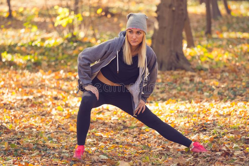 Portrait of a full section of an attractive motivated athletes. Portrait of a full section of an attractive motivated athletes who stretch their legs in the royalty free stock image