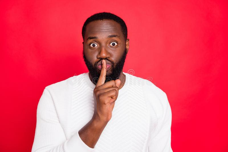Portrait of funky cunning african mulatto man show index finger near his mouth face ask dont share private information. Portrait of funky cunning african mulatto stock photos