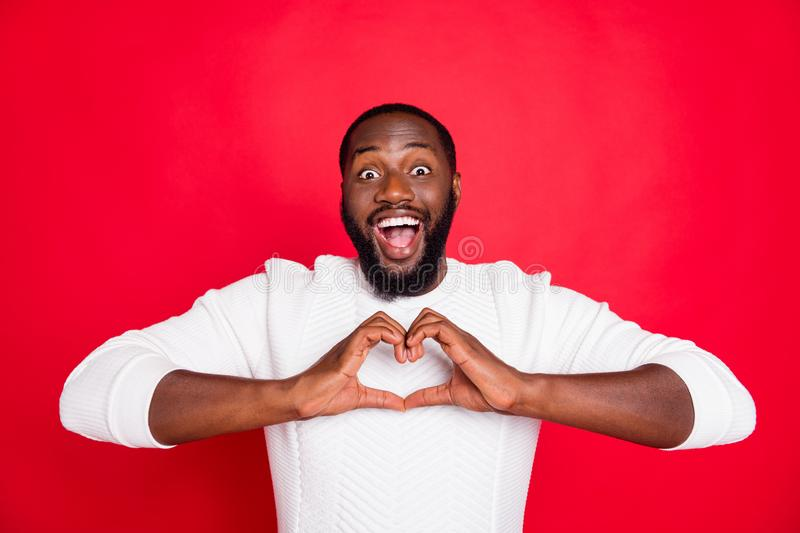 Portrait of funky positive cheerful mulatto guy show love sign make heart with his fingers enjoy date with girlfriend. Portrait of funky positive cheerful royalty free stock photography