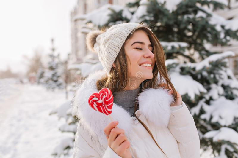 Portrait funny amazing girl enjoying winter time, holding lollypop on street. Brightful happy emotions of young woman in. Warm white winter clothes with closed royalty free stock photos
