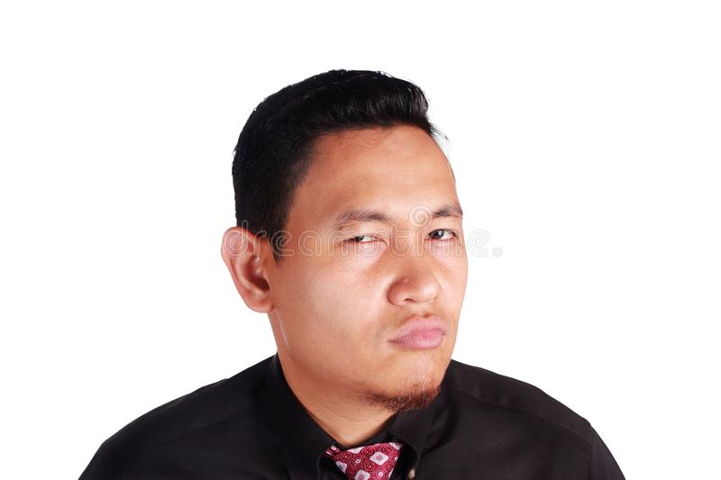 Cynical Asian businessman looking to camera with anger. Portrait of funny Asian businessman showing cynical angry facial expression, isolated on white stock photography