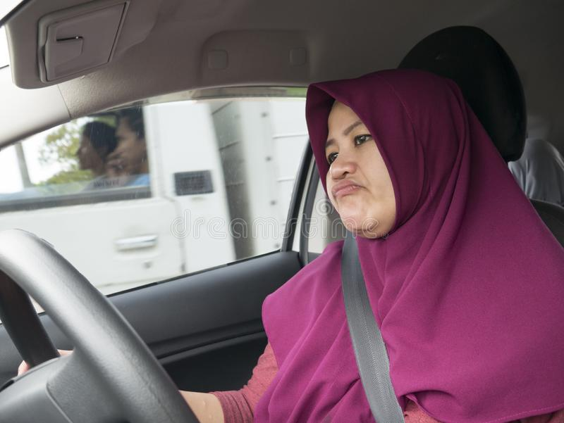 Female Driver Get Bored in Her Car. Portrait of funny Asian female muslim driver get bored in her car trapped in traffic jam, tired lazy facial expression royalty free stock photography