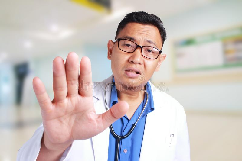 Funny Doctor Saying Bad News, Calming His Patient. Portrait of funny Asian male doctor calming patient, telling bad news royalty free stock image