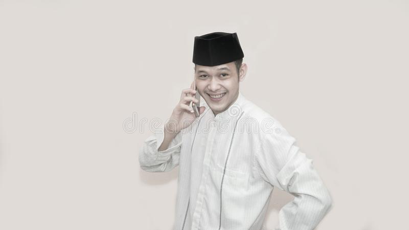 Portrait of Funny an asian muslim man with head cap taking a call stock image
