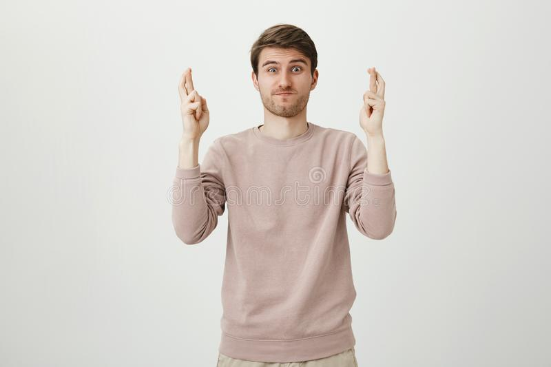 Portrait of funny attractive caucasian man raising hands with crossed fingers, holding breath and lifting eyebrows. Desiring something over gray background royalty free stock images