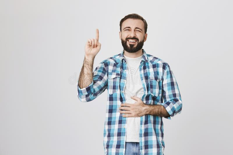 Portrait of funny bearded man holding index finger up, showing eureka gesture, while another hand on belly because of. Laughing out loud. Guy make jokes and he royalty free stock photo