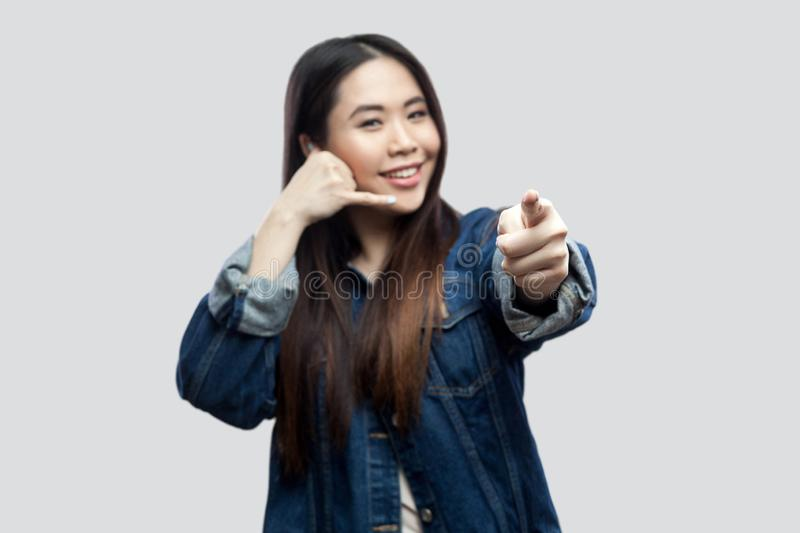 Portrait of funny beautiful brunette asian girl in casual blue denim jacket makeup standing with call gesture, looking and stock photography