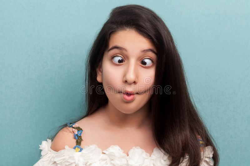 Portrait of funny beautiful brunette young girl with black long straight hair in white dress standing with crossed eyes, fish lips. And crazy expression. indoor royalty free stock image