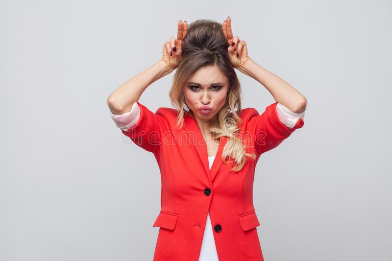 Portrait of funny beautiful business lady with hairstyle and makeup in red fancy blazer, standing with bully gesture on head and royalty free stock photo