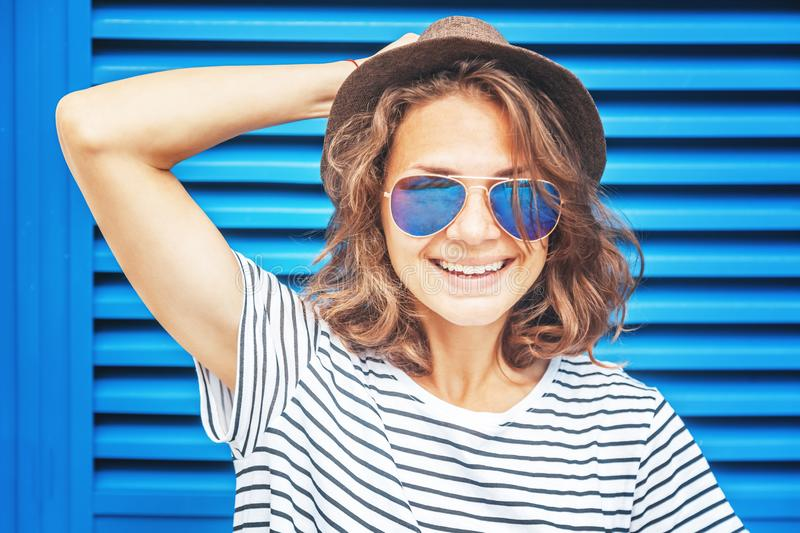 Portrait of a funny beautiful happy hipster girl wearing a hat a stock images