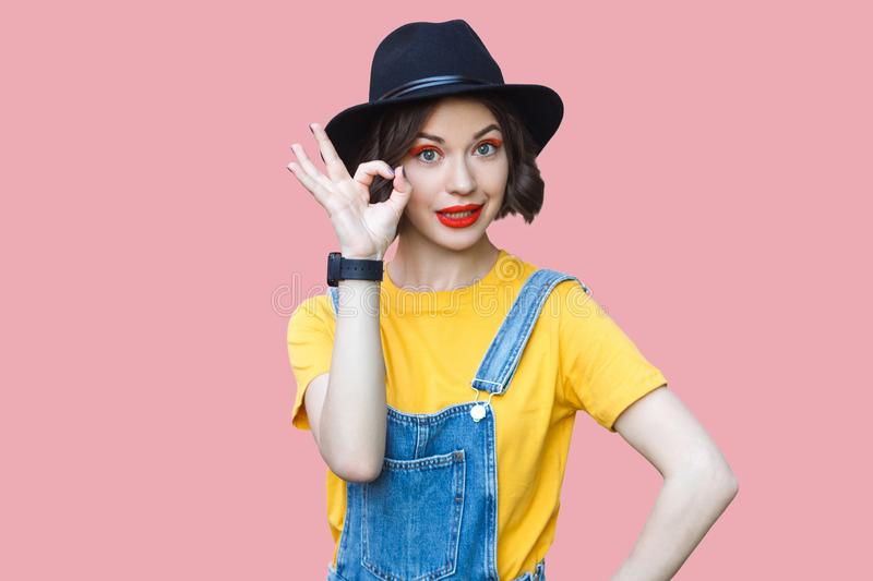 Portrait of funny beautiful young woman in yellow t-shirt and blue denim overalls with makeup and black hat standing with ok sign stock photos