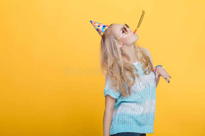 Portrait of funny blond woman in birthday hat and blue shirt on yellow background. Celebration and party. Having fun stock photography