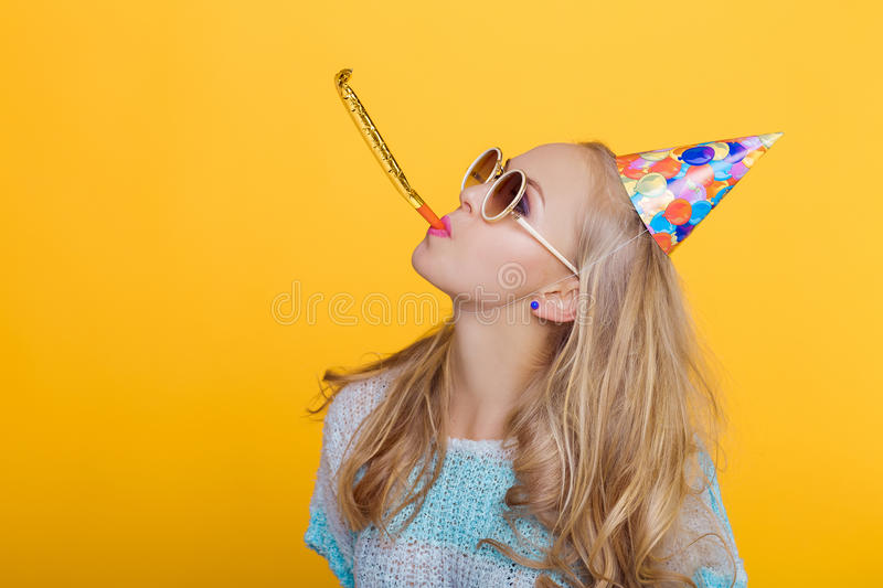 Portrait of funny blond woman in birthday hat and blue shirt on yellow background. Celebration and party. Having fun stock images
