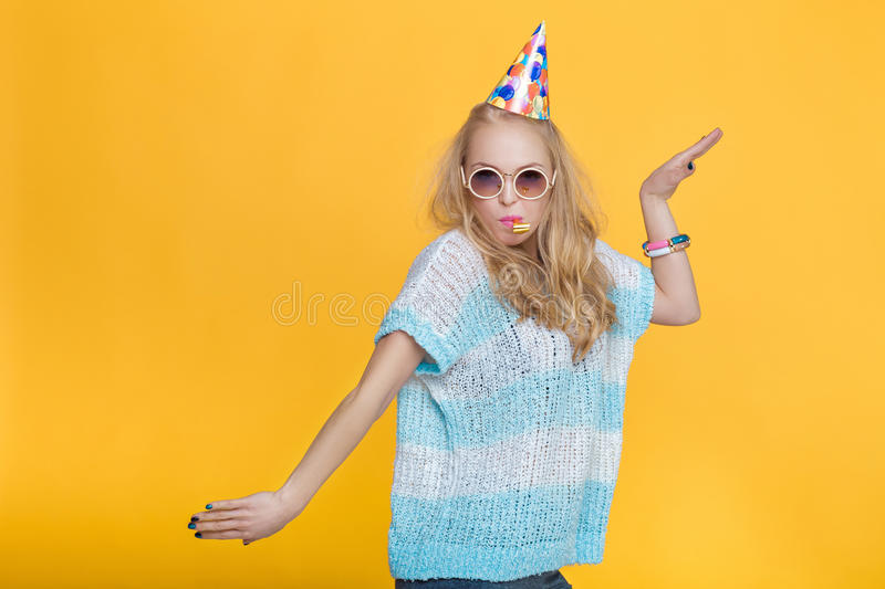 Portrait of funny blond woman in birthday hat and blue shirt on yellow background. Celebration and party. royalty free stock photo