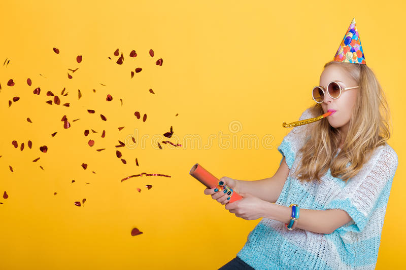 Portrait of funny blond woman in birthday hat and red confetti on yellow background. Celebration and party. royalty free stock images