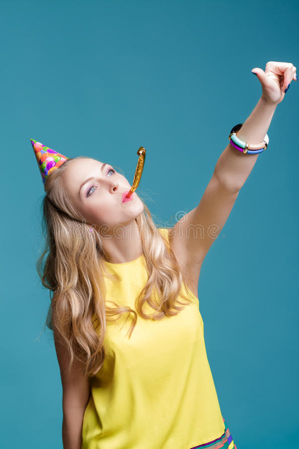 Portrait of funny blond woman in birthday hat and yellow shirt on blue background. Celebration and party. Having fun stock image