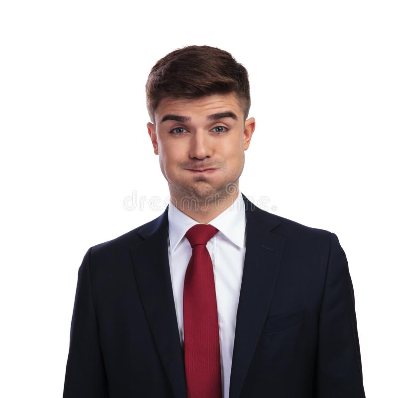 Portrait of funny businessman making a goofy face. While standing on white background. He is wearing a navy coloured suit and a red tie royalty free stock photos