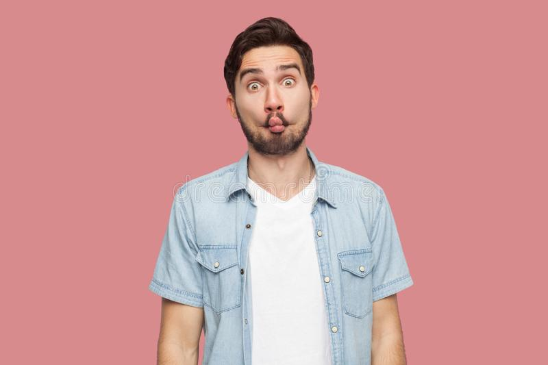 Portrait of funny comic face handsome bearded young man in blue casual style shirt standing with fish lips and looking at camera stock photo