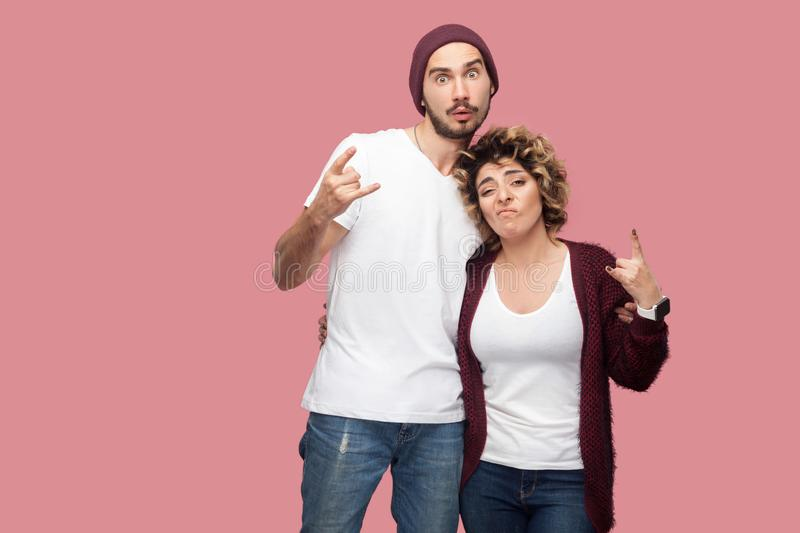 Portrait of funny couple of friends in casual style standing, hugging each other and showing rock and roll hand sign gesture,. Looking at camera. Isolated royalty free stock photos