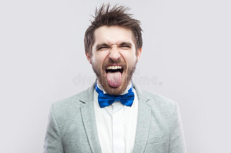 Portrait of funny crazy handsome bearded man in casual grey suit and blue bow tie standing with closed eyes and tongue out excited. Indoor studio shot, on stock image