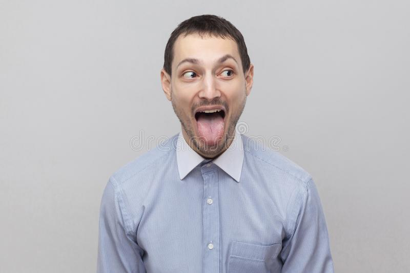 Portrait of funny crazy handsome bristle businessman in classic light blue shirt standing and looking aside with tongue out and. Big eyes. indoor studio shot stock photography