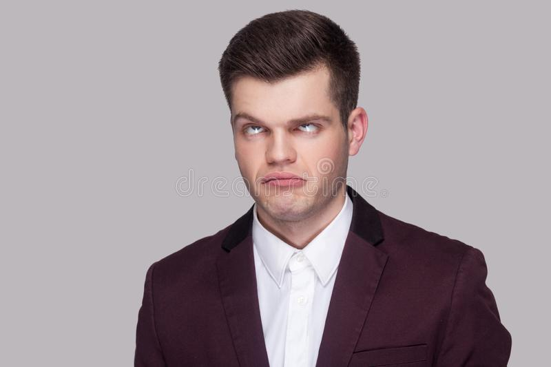 Portrait of funny crazy handsome young man in violet suit and white shirt, standing, looking with crossed eyes and foolish face. royalty free stock photography