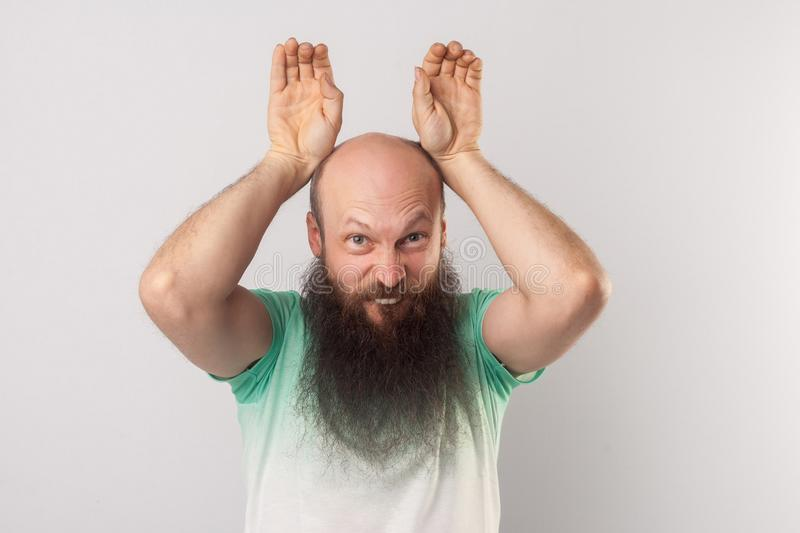 Portrait of funny crazy middle aged bald man with long beard in light green t-shirt standing with bunny ears gesture and looking stock photography