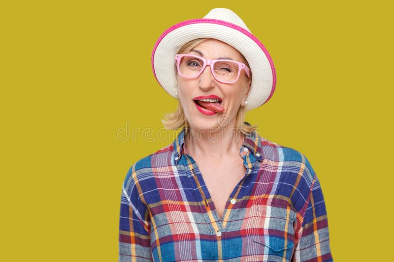 Portrait of funny crazy modern stylish mature woman in casual style with hat and eyeglasses standing, winking, tongue out and. Looking at camera. indoor studio royalty free stock photos