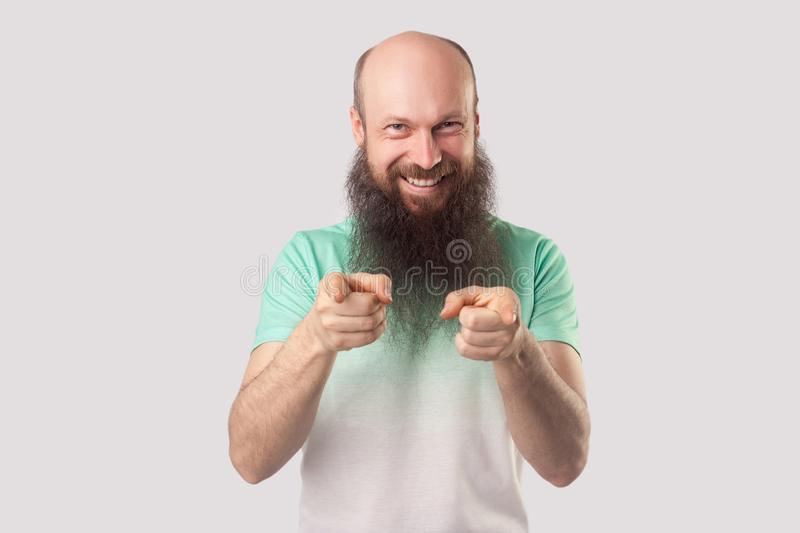 Portrait of funny excited middle aged bald man with long beard, green t-shirt standing, pointing and looking at camera with toothy royalty free stock image