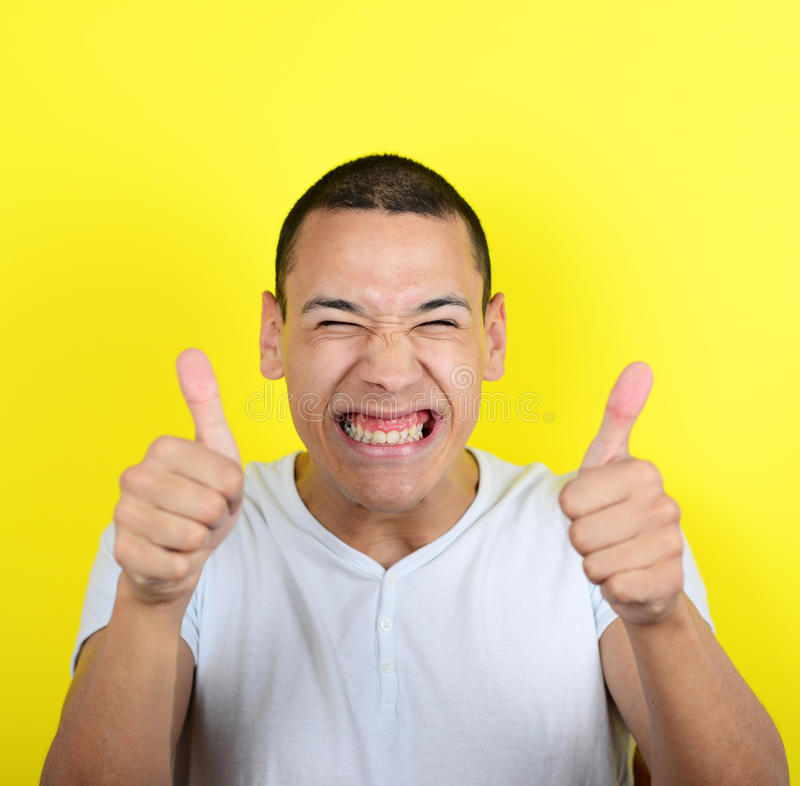 Portrait Of With Funny Expression Holding Thumbs Up Against Yell Stock Photo