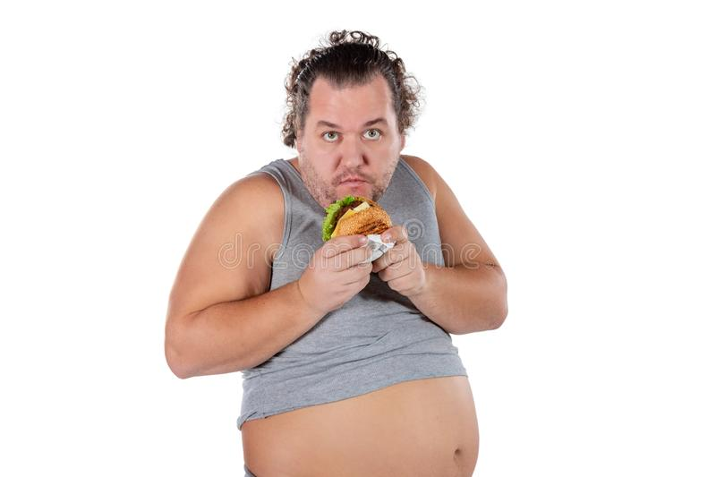 Portrait of funny fat man eating fast food burger isolated on white background stock photos
