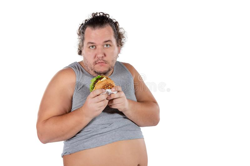 Portrait of funny fat man eating fast food burger isolated on white background stock image