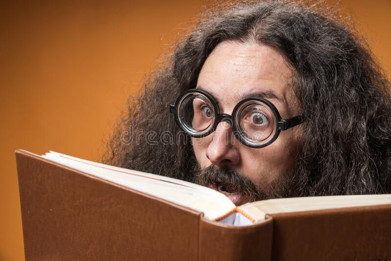 Portrait of a funny geek reading a book stock photography