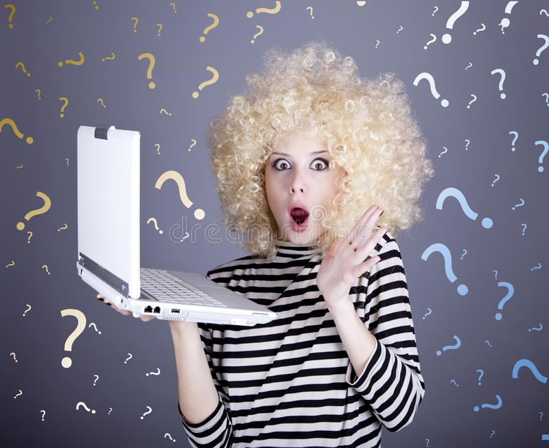 Portrait of funny girl in blonde wig with laptop. stock photos