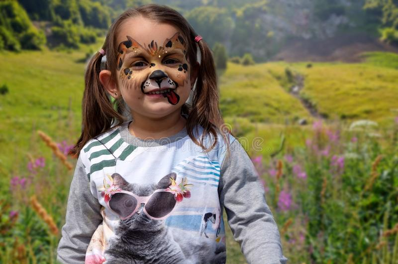 Portrait of funny girl with face painting on blurred greenery background.  royalty free stock photo