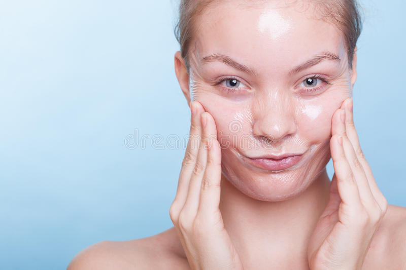 Portrait funny girl in facial peel off mask. Beauty skin care. Portrait of funny blond girl young woman in facial peel off mask. Peeling. Beauty and body skin stock image