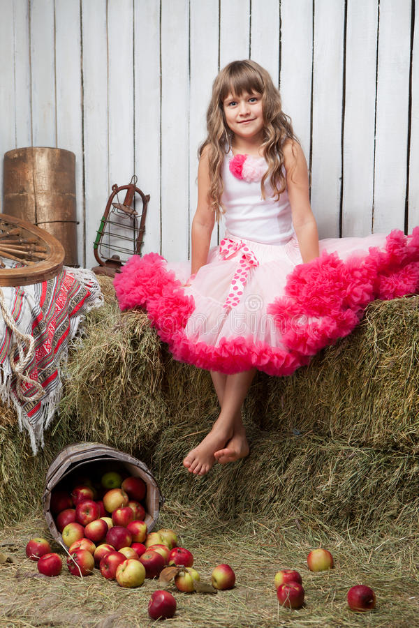 Portrait of funny girl near pail with apples. Portrait of barefooted funny little blond girl, villager dressed luxuriant wavy ball dress with frill sitting on royalty free stock image