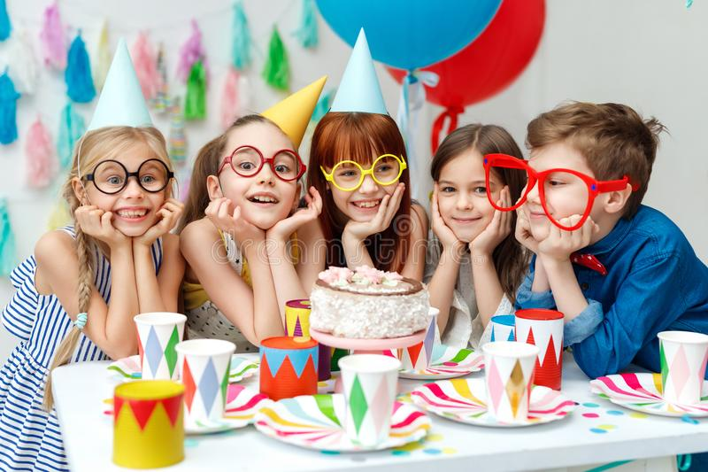 Portrait of funny group of children wear party caps, big spectacles, look with big appetite on birthday cake, want to. Taste it, have special occasion, spend stock photos